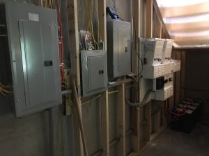 Breaker boxes and battery inverter wall by Keowee Home Solar